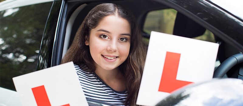 girl holding learner plates in car