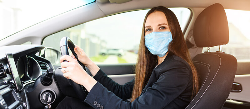 woman wearing face mask in car